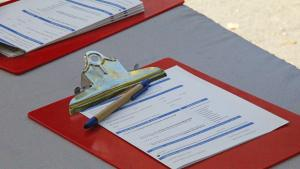 Oregon Voter Registration Card on a red clipboard sits on a table at an outreach event, waiting to be filled out.