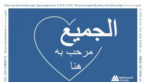 All Are Welcome Here Arabic language sign.  A heart in blue and white with the Multnomah County logo.