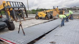 Installing new steel grate deck on Morrison Bridge lift span. It will be filled with concrete this summer.