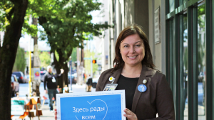 Multilingual Elections worker holds Russian language sign outside elections office.  All Are Welcome Here.  Sign in blue and white with heart and Multnomah County logo.