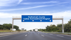 Road sign that reads Multnomah County Justice Reinvestment Program