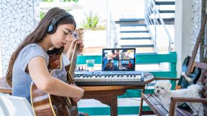 Teen girl playing guitar with friends via teleconferencing