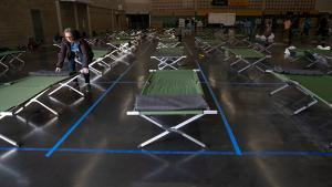 photo of someone setting up cots at the Oregon Convention Center social distancing shelter.