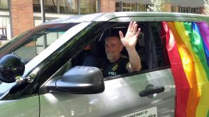 A DCJ staff member waves while driving a DCJ vehicle in the 2016 Pride Parade.