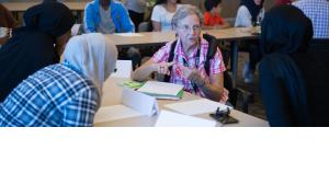 A volunteer talks about social services at Catholic Charities' cultural orientation class for new refugees