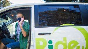 A driver wearing a cloth mask waves from the front seat of a white van bearing the Ride Connections logo.