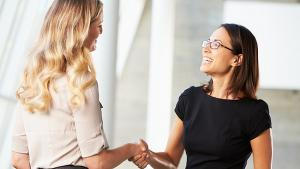 Two well dressed women shaking hands