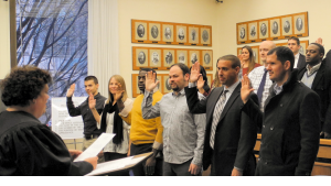 Group of adults raising their right hands