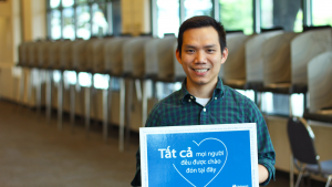 Bilingual elections worker holds Vietnamese language sign, All Are Welcome Here inside the elections office.  Sign in blue and white with a heart and Multnomah County logo.