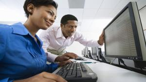 photo of woman at computer with man