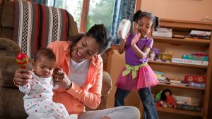 mom, young child and baby playing in their living room