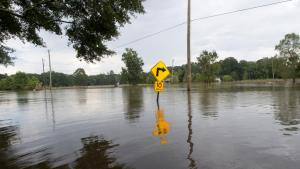 Road covered in water with street sign in the middle of the image
