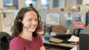 woman at desk with headset making a call