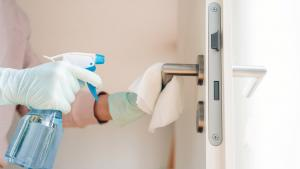 spraying disinfectant on a door handle