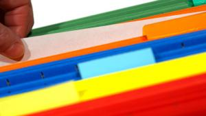 photo of someone with a document and colorful folders