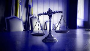 photo of scales of justice on table in courtroom