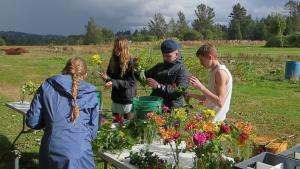 Four youth arranging flowers at a table in a field.