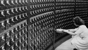 Person trying to find a record in an old card catalog.