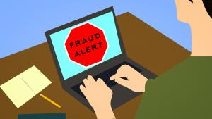 """Person at desk with a laptop computer; words on computer screen say, """"FRAUD ALERT""""."""