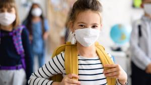 girl standing in a school hallway, wearing a mask