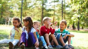 Picture of kids eating while sitting on the ground