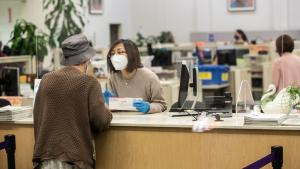 Image of an employee helping a Multnomah County residents at the elections office. Both people are wearing masks.