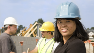 Hispanic woman at construction site wearing a hard hat