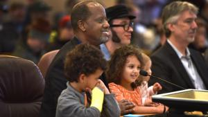 Kayse Jama urged commissioners to pass the e-cigarette ordinance while holding his children. On his left, another father, and vape shop owner Paul Bates, asked the board for exemptions