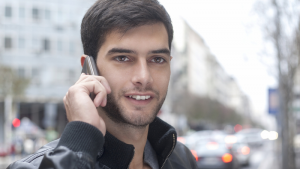 Man standing on street talking on cell phone