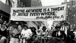 """Image of disability rights protesters carrying a banner that says, """"Injustice anywhere is a threat to justice everywhere."""" Dr. Martin Luther King, Jr."""