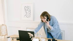 Image of woman standing over a laptop and talking on a cell phone.