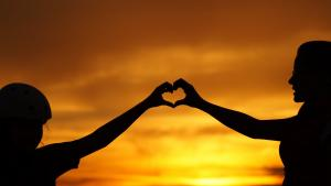 Silhouettes of two people extending their arms up and forming a heart shape with their hands with a sunset in the background