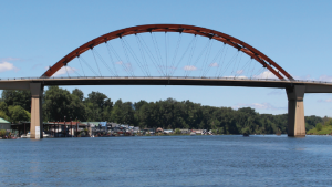 Sauvie Island bridge with river in the foreground, and houseboats and blue sky in the background.