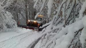 Snowplow clearing a road of foot-deep snow, surrounded by bare tree branches weighed down with snow.
