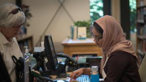Suad Mohamed helps a patrol at Capitol Hill Library