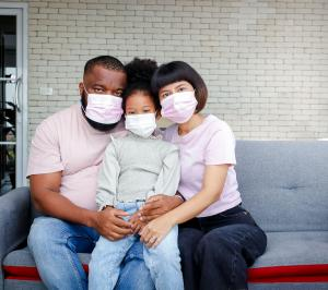 A family, two parents and a child, sit together on a couch on their front porch; they are wearing masks to protect themselves and others from COVID-19