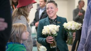 Stacy Borke of Transition Projects accepts donated roses for the opening.