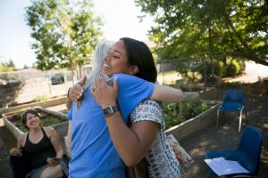 Patient Sandra Howe hugs community health worker Fanny Rodriguez, who recently married her longtime sweetheart.