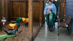 Andrea Bunch watches as her son, Michael, 4, reacts to the playground equipment just outside their new apartment.