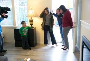 Michael Bunch talks with a reporter and team members from ekoLiving, which is offering the apartment he and his mother moved into.