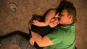 Stephanie Ramirez hugs her daughter Surri Noelle on the living room carpet in their new apartment.