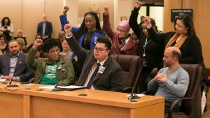Multnomah County Employees of Color ERG members raise their fists in solidarity at the Thursday's board meeting.