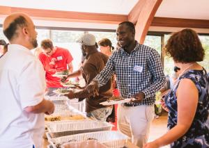 Thomas Aquinas Debpuur, (center) who works for IRCO's Africa House, shares a meal with other forum participants.