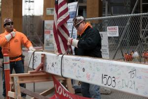 Worker prepares beam for lift to it's final resting place