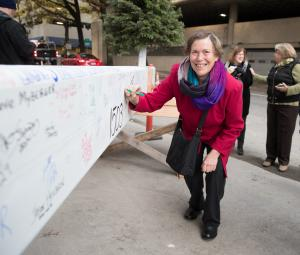 Former Commissioner and early supporter of courthouse project Judy Shiprack signs the courthouse beam.