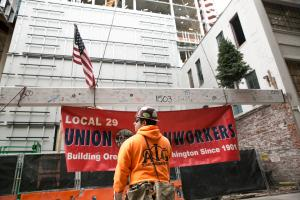 Following an ancient tradition started by European builders, a small tree was attached to the beam, to honor the natural resources that contributed to this human-built structure. A United States flag and a banner for the local ironworkers union