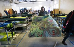 Patricia Rojas, deputy director of the Joint Office of Homeless Services, rolls out a carpet at the winter family shelter on Dec. 3, 2018.