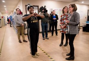 Sean Williams makes a heart with her hands after showing her dance moves to Gov. Kate Brown and Chair Deborah Kafoury at the Gresham Women's Shelter on Dec. 17, 2019.