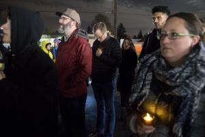 Marc Jolin, center, listens as the names of those who died are read.