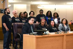 Employees of Color (EOC) Employee Resource Group Co-Chair Raymond de Silva addresses the Board surrounded by his fellow EOC members.